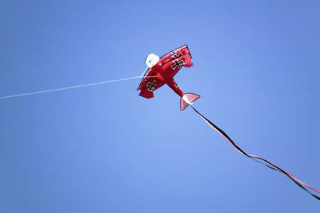 An airplane shaped red kite flying in a deep blue sky on April 15, 2007, at the Santa Barbara Kite Festival, Santa Barbara City College, overlooking Pacific Ocean. Editöryel