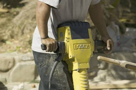 Man breaking concrete with yellow jackhammer