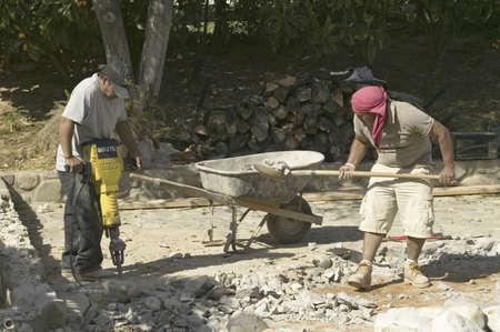 presslufthammer: Hispanic M�nner brechen Beton mit gelben Presslufthammer und Schaufel Felsen