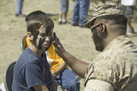 solider: Army solider applying camouflage to young boy at the 42nd Naval Base Ventura County (NBVC) Air Show at Point Mugu, Ventura County, Southern California.
