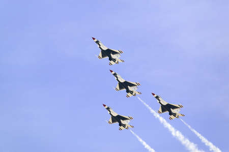Four US Air Force F-16C Fighting Falcons, known as the Thunderbirds, flying in formation with white trailer of smoke over the 42nd Naval Base Ventura County (NBVC) Air Show at Point Mugu, Ventura County, Southern California.