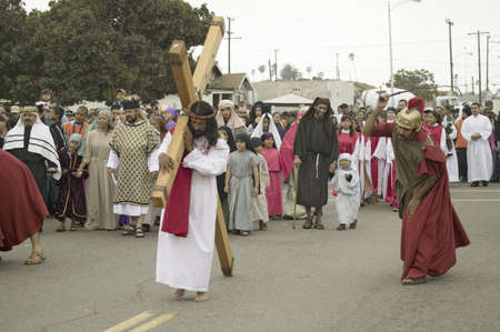 Roman soldiers overseeing reenactment of Jesus Christ carrying a cross past crowds on Good Friday, Easter, during the Passion play, a dramatic portrayal of the trial, torture and death of Jesus Christ at Christ the King Church and Our Lady of Guadalupe Pa Stock Photo - 20801662
