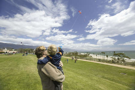 flying man: Father and son flying a kite in a deep blue sky on April 15, 2007, at the Santa Barbara Kite Festival, Santa Barbara City College, overlooking Pacific Ocean. Editorial