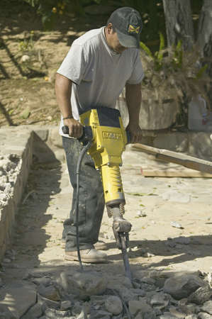Hispanic male breaking concrete with yellow jackhammer