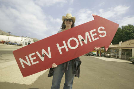 to paula: Girl holding red sign with arrow pointing up, that reads New Homes For Sale in Santa Paula, California Editorial