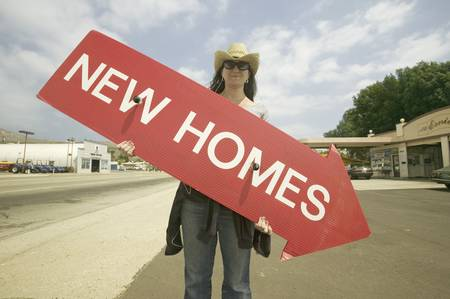 Girl holding red sign with arrow pointing down, that reads New Homes For Sale in Santa Paula, California