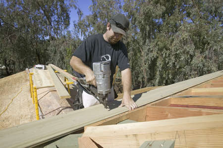 tongue and groove: Carpenter nailing tongue & groove board on roof on new house construction, Ojai, California