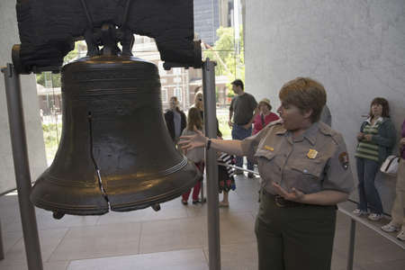 A National Park Ranger explaining the crack in the Liberty Bell in Liberty Bell Center, Philadelphia, Pennsylvania