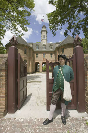 reenactor: 18th Century reenactor standing at front gate of the Capitol Building of Colonial Williamsburg, Virginia. In this building Patrick Henry, George Washington, George Mason, George Wythe, Richard Henry Lee, Jefferson, and others played their parts in the leg
