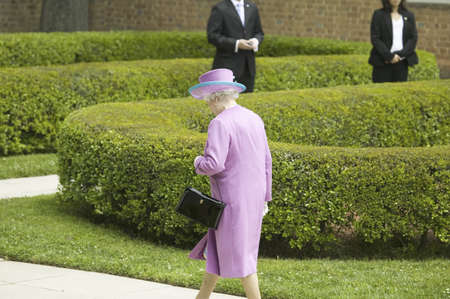 Her Majesty Queen Elizabeth II in bright purple outfit and black purse, walking alone down sidewalk to Governors Palace in Williamsburg Virginia, as part of the 400th anniversary of the English Settlement of Jamestown, Virginia, May 4, 2007