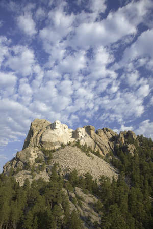 White puffy clouds behind Presidents George Washington, Thomas Jefferson, Teddy Roosevelt and Abraham Lincoln at Mount Rushmore National Memorial, South Dakota