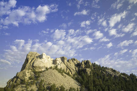 busts: White puffy clouds behind Presidents George Washington, Thomas Jefferson, Teddy Roosevelt and Abraham Lincoln at Mount Rushmore National Memorial, South Dakota Editorial