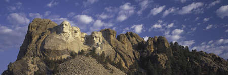 Panoramic image with white puffy clouds behind Presidents George Washington, Thomas Jefferson, Teddy Roosevelt and Abraham Lincoln at Mount Rushmore National Memorial, South Dakota