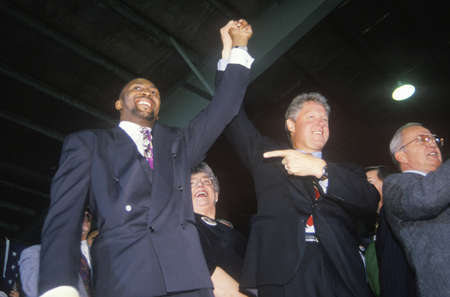 campaigning: Governor Bill Clinton joins hands with Boxer Tommy Heams during a Detroit campaign rally in 1992 on his final day of campaigning in Detroit, Michigan