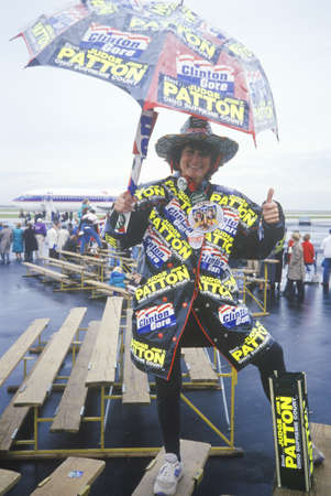 Woman shows off ClintonGore stickers on her rainwear, 1992