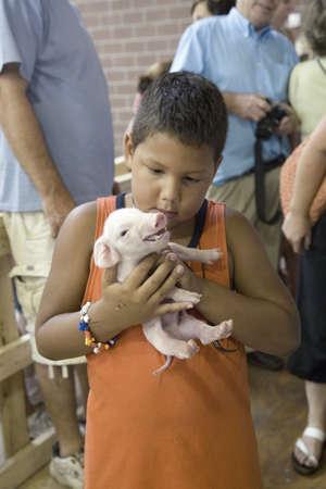 iowa: Latino boy holding baby pig at Iowa State Fair, Des Moines, Iowa, August, 2007 Editorial