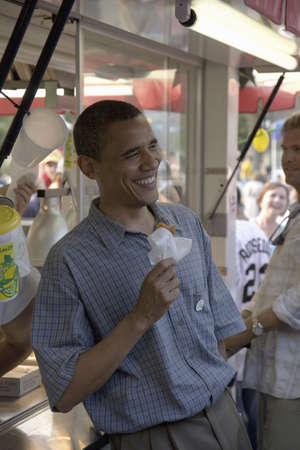 campaigning: U.S. Senator Barak Obama eating corn dog while campaigning for President at Iowa State Fair in Des Moines Iowa, August 16, 2007