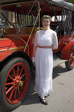 to paula: Woman in Victorian dress standing in front of antique car in Santa Paula, CA Editorial