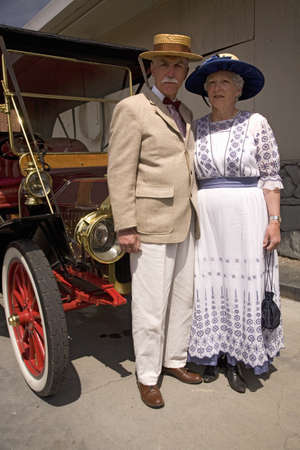 Dressed up couple in old-fashioned clothing standing in front of antique car in Santa Paula, CA