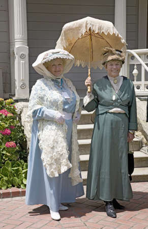 to paula: Women in Victorian dresses standing on porch of Faulkner Farm and Victorian home in Santa Paula, CA
