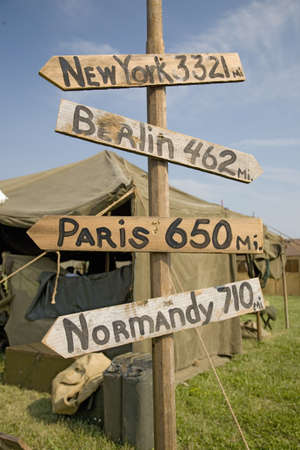 totals: World War II replica signs to New York, London, Berlin and Normandy with mileage totals in front of tents at Mid-Atlantic Air Museum World War II Weekend and Reenactment in Reading, PA held June 18, 2009