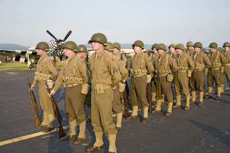 World War II Infantry troops standing at attention with sunset light on them at Mid-Atlantic Air Museum World War II Weekend and Reenactment in Reading, PA held June 18, 2008