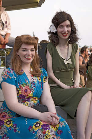 world war ii: Two women smile as they are dressed in World War II 1940s vintage dresses at Mid-Atlantic Air Museum World War II Weekend and Reenactment in Reading, PA held June 18, 2008