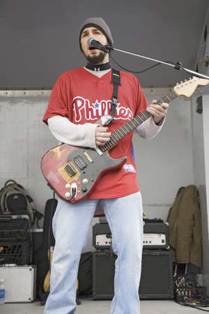 brotherly love: Rock band guitarist with Philadelphia Phillies baseball top playing music in front of Citizens Bank Park, opening game, March 31, 2008 of the Philadelphia Phillies Major League Baseball team.