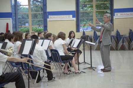 Grade school band conductor leading school 5th grade band recital at Ravensworth Elementary, Fairfax County, Springfield, Virginia