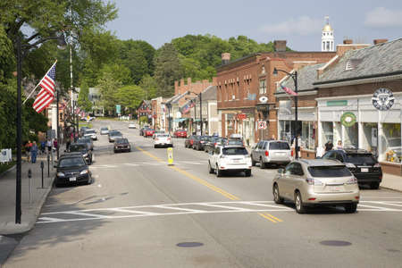 Storefronts in historic Concord, MA on Memorial Day Weekend with American Flags displayed