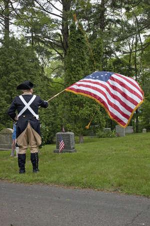reenactor: Un revolucionario honores Reenactor muertos con una bandera americana fuera de Lexington, MA en Memorial Day de 2011 Editorial