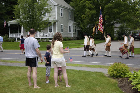 Family in front yard wave flags as they watch Concord Minutemen Revolutionary reenactors march down road to Concord, MA on Memorial Day, 2011 Stock Photo - 23231109
