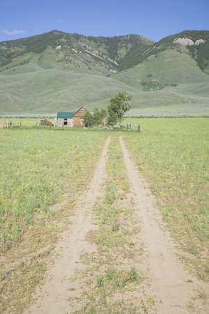 Dirt driveway leads to western home up against mountains, Idaho