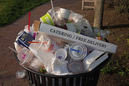 Overflowing trash can with empty Pizza box saying CateringFree Delivery in Lexington, MA