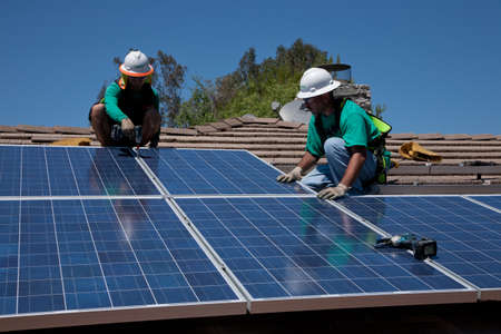 photovoltaic: Workers installing a solar panel on a rooftop