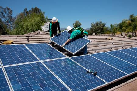 panel: Workers installing a solar panel on a rooftop Editorial