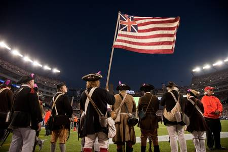 Gillette Stadium, Foxborough, MA - October 16, 2011 - People dressed up in patriot costumes holding a Grand Union flag