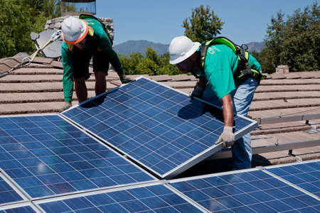Workers installing a solar panel on a rooftop