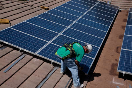 A worker arranging solar panels on the rooftop