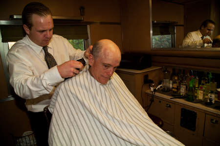 reenactor: Photographer Joseph Sohm getting a haircut in the barbershop on Pearl Harbor Day Troop Train re-enactment from Los Angeles Union Station to San Diego