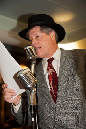 historic world event: A man dressed up in 1940s attire using a microphone on Pearl Harbor Day Troop Train re-enactment from Los Angeles Union Station to San Diego  Editorial