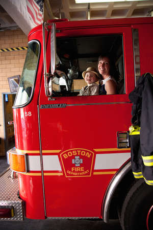 north   end: North End, Boston, MA - May 11, 2012 - Mother and son sitting in a stationary fire truck at Ladder No 1 & Engine No 8 fire station