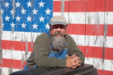 augusta: Augusta, Maine - 10 de junio de 2012 - Un hombre de pie ancianos delante de una bandera de EE.UU. pintada en su cobertizo Editorial