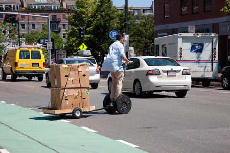north   end: North End, Boston, MA - June 15, 2012 - Segway PT hauling a trailer while crossing the road  Editorial