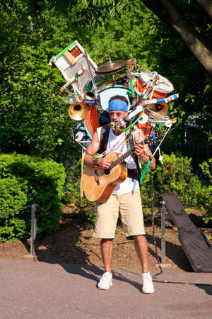 One-man band musician playing instruments at Public Garden in Boston, Massachusetts