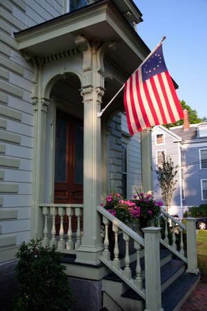 front porch: Colonial flag hanging on front porch of home in Newburyport, Massachusetts