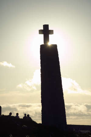 Cross with sun behind it at Cabo da Roca on the Atlantic Ocean in Sintra, Portugal, the westernmost point on the continent of Europe, which the poet Cam›es defined as where the land ends and the sea begins. Editorial
