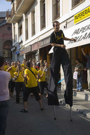 Man on stilts and marching band making their way down the streets of Puigcerda, Girona, Cataluna, Spain, Europe
