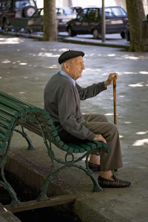 Older man with cane sitting on bench in market area of La Seu dUrgell, (Sa Seu dUrgell) in Catalunya, Spain