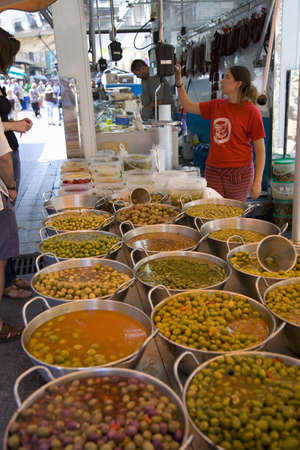 spaniards: Woman weighing food with olives in foreground of La Seu dUrgell, (Sa Seu dUrgell) in Catalunya, Spain Editorial